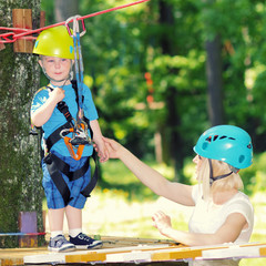 little boy in a special outfit for climbing scared