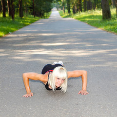 woman doing push-ups during outdoor cross training