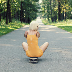 Girl sitting on a skateboard back on the road outdoors.