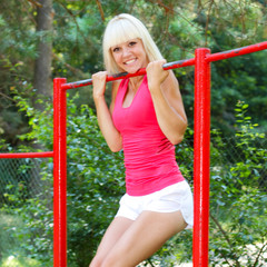 beautiful fitness woman doing exercise on bars outdoor.