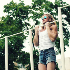 beautiful fitness model man doing exercise on bars outdoor.