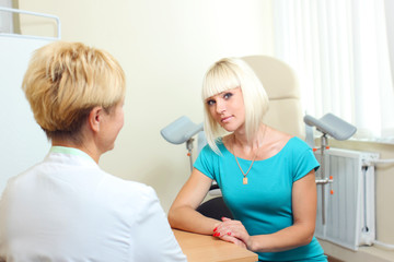 Woman patient talking to a gynecologist gynecology office.