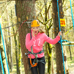 positive cheerful girl having fun doing tree climbing.