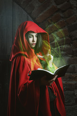 Red hooded woman with magical book