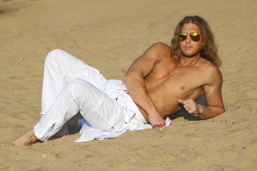 Fitness model man with long hair  posing on the beach