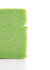 Green cheese with holes on a white background