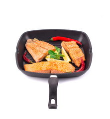 Frying pan of three salmon steaks and red peppers