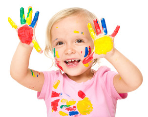 Portrait of a cute little girl playing with paints
