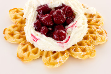 Cream and sour cherries on fresh baked waffle
