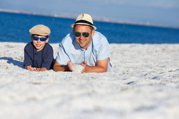 Happy father and son having fun at beach