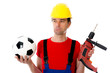 worker with drilling machine and soccer ball