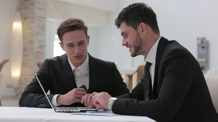 Two businessmen are talking in front of a laptop