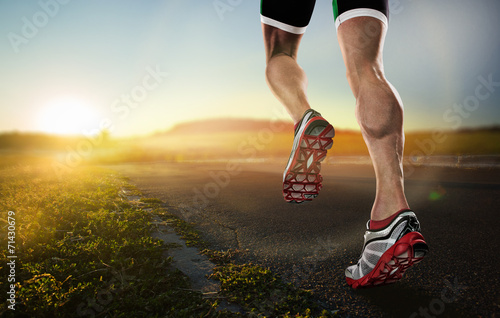 Leinwandbild Motiv Sports background. Runner feet running on road closeup on shoe.