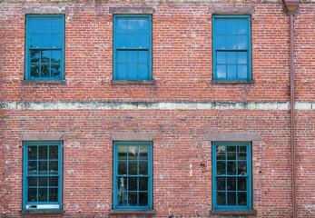Six Green Windows on Old Brick Building
