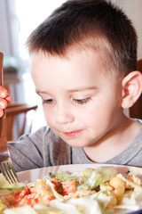 little boy at the kitchen table with food