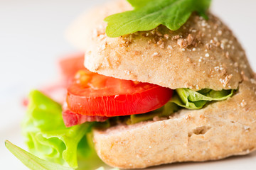Salami sandwich with tomato and arugula