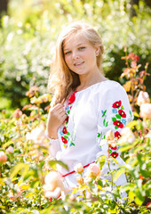portrait of blonde ukrainian girl in national clothes at meadow