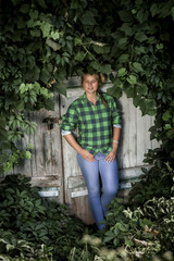 girl in jeans and checkered shirt leaning against barn door