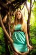 beautiful blonde woman sitting on liana at rain forest