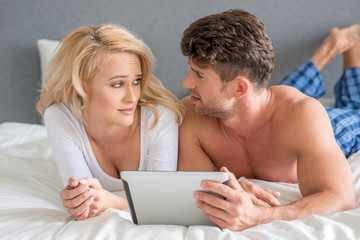 Couple Lying in Bed Arguing While Using Tablet