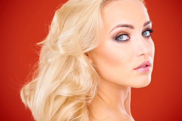 Close Up of Blond Woman Against Red Background