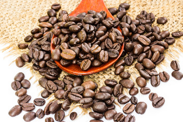 coffee beans on sacking and wood spoon, white background