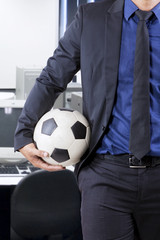 Businessperson holding ball in office