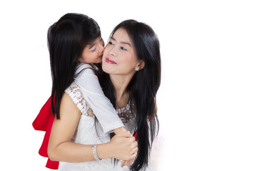 Child embraces and kiss her mother