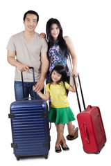 Family with luggage in studio