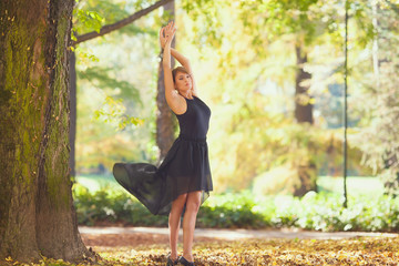 Attractive female dancing in nature on beautiful autumn day.