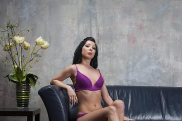 Frau in lila Unterwäsche auf einer Couch