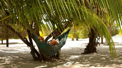 Happy Woman Relaxing on Hammock on the Beach.