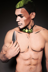 muscular man with painted face and chest with dagger