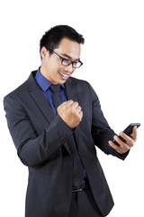 Satisfied businessman holding mobile phone