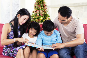 Two parents help their children to read