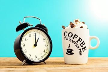 Black old clock and coffee mug with cream.