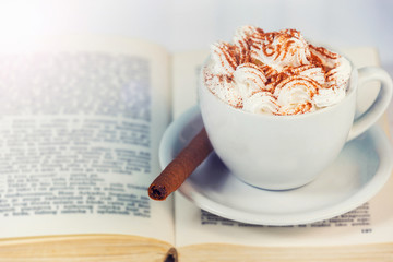 White cup of coffee, cream and cookie on book.