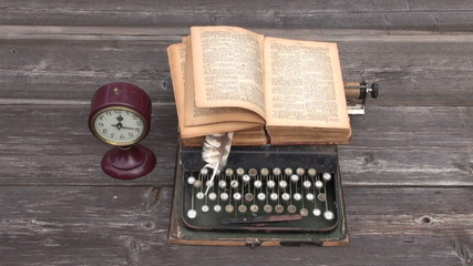 ancient typewriter and old book on wooden background