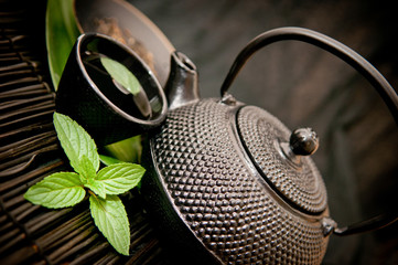 Black iron asian teapot with sprigs of mint