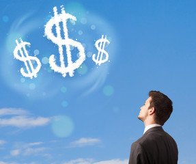 Businesman pointing at dollar sign clouds on blue sky