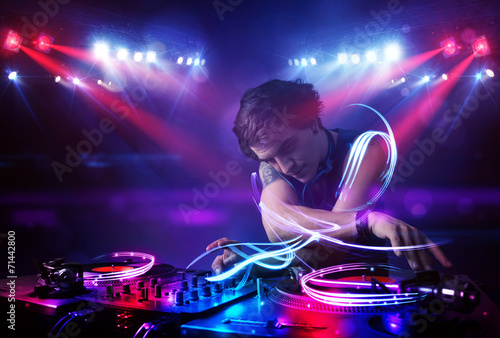 Leinwanddruck Bild Disc jockey playing music with light beam effects on stage