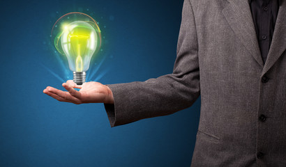 Glowing lightbulb in the hand of a businessman