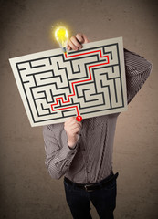 Businessman holding a paper with a labyrinth on it in front of h