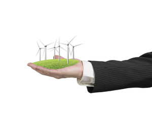man hand holding group of windmills on grass
