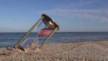 brass ancient hourglass sandglass clock on sea beach sand