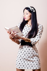 pinup girl in polka dot white dress reading book