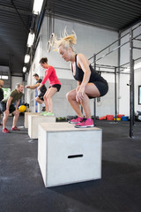 Workout group trains box jumps at the fitness gym