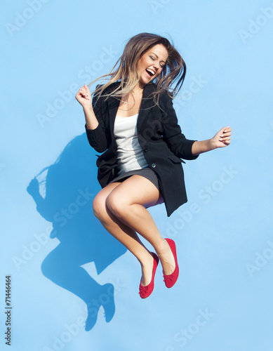 Successful young attractive laughing woman jumping up - 71446464