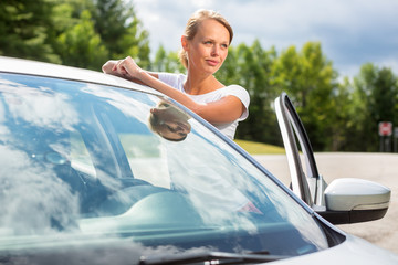 Young, attractive, happy woman standing by her car
