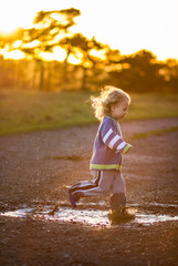young toddler running through puddles